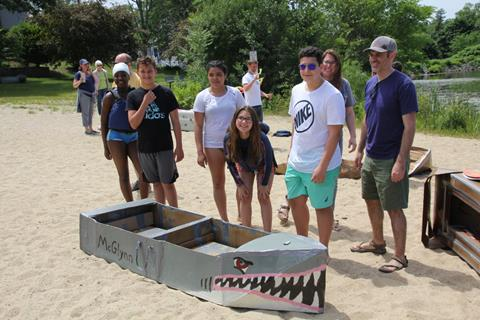 A group of students standing with their shark themed cardboard canoe