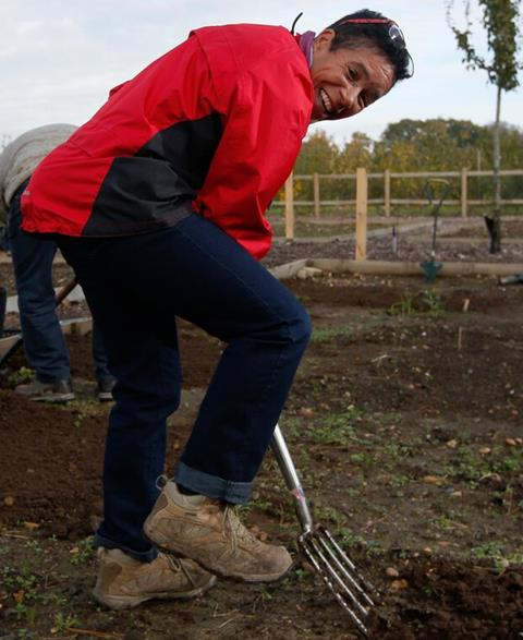 A woman wearing a red jacket uses a garden spade to dig the soil.