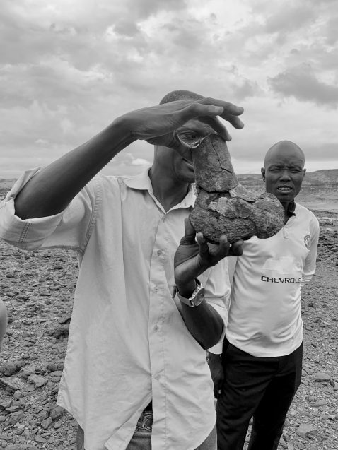 Francis Ekai Ikai, a fossil finder at the Turkana Basin Institute, holds up a fossil hippo femur from the Lothagam geologic formation, near Kenya's Lake Turkana. Looking on, his colleague Julius Kerio. (Sophia Lee)