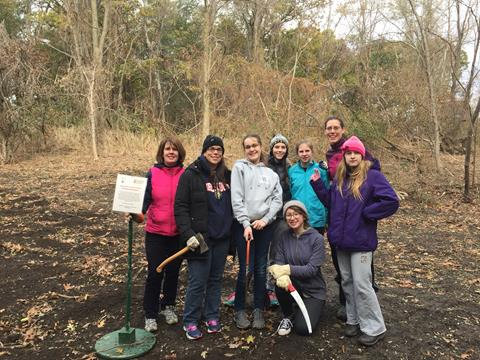 Girl Scouts and their leaders standing in a clearing with their tools