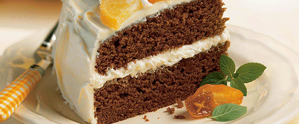Slice of chocolate cake with white frosting and fruit on the side.