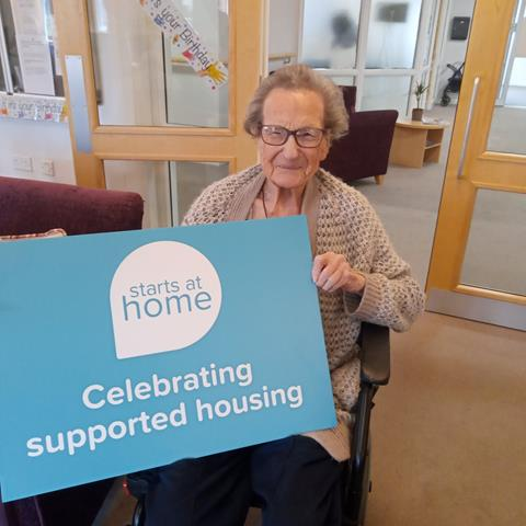 Resident at Bowles Lodge holding Starts at Home Day sign