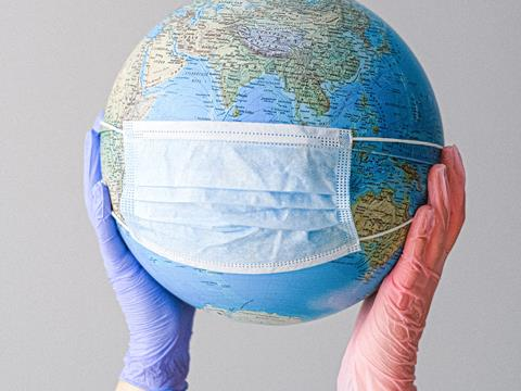Picture of rubber gloves holding a globe wearing a mask