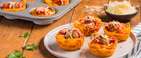 Photo of muffin tins of spaghetti wrapped around meatballs with grated parmesan on the side.