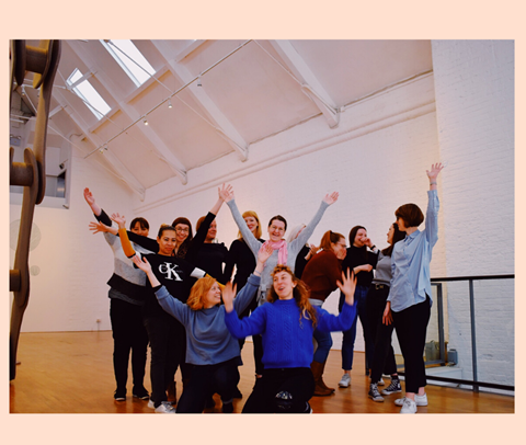 A group of women stand and kneel together, some are laughing and have their hands in the air. They are in a large white room with a high ceiling, a grey chain. sculpture is just visible on the left hand side.