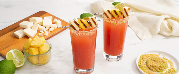 Photo of Two Caesar drinks on a marble counter with extra cheese, fruit and seasoning surrounding them.