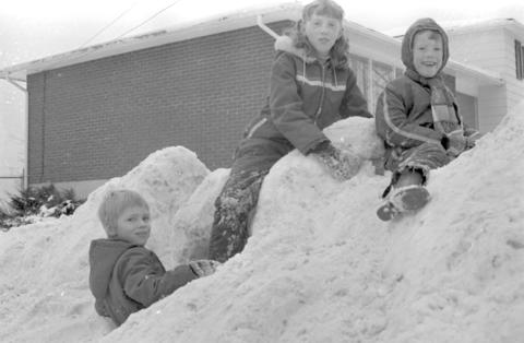 This is an picture from the library archives. It is of three children sitting on top of a snowbank in January of 1980.