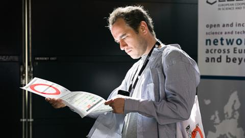 A man looking at the programme for ESOF