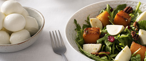 Photo of Butternut Squash and Bocconcini Salad on a white table cloth with a bowl of Bocconcini balls.