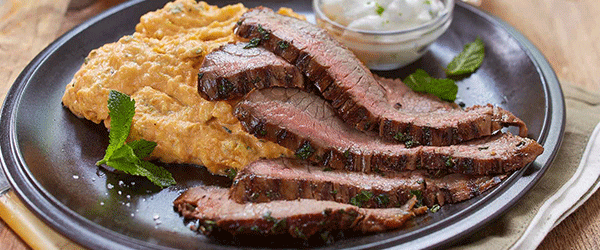 A plated flank steak with mashed sweet potatoes