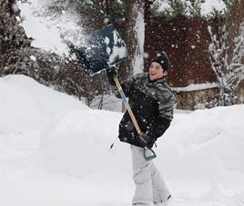 A teenager has fun clearing snow by throwing it at someone off-camera.