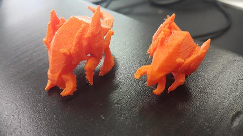 This is a photograph of two orange dragons created on the 3D printer.