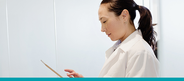 Une femme en blanc lit sur sa tablette