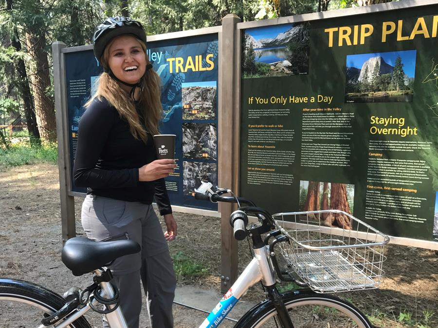 A helmet-wearing biker poses next to a Yosemite Bike Share bike, holding a cup of coffee from our sponsor, Peet's Coffee.