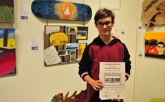 Boy holding certificate near artwork
