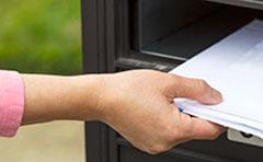 Photo of a resident collecting rate notice from letter box