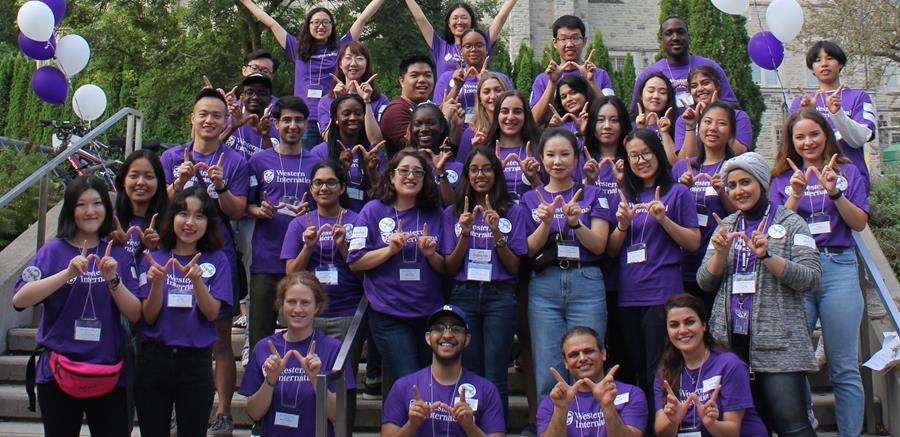 Students wearing purple making the letter 'W' with their hands