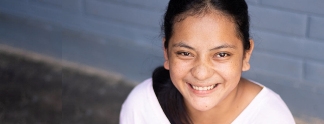 A smiling girl with black hair and light brown skin
