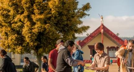Image of different people in front of a Marae