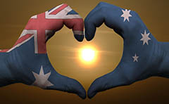 Photo of hands painted in the Australian flag in heart shape around a sunrise