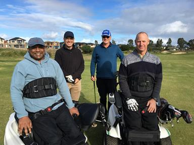 Group of men playing golf. Two of them are in wheelchairs.