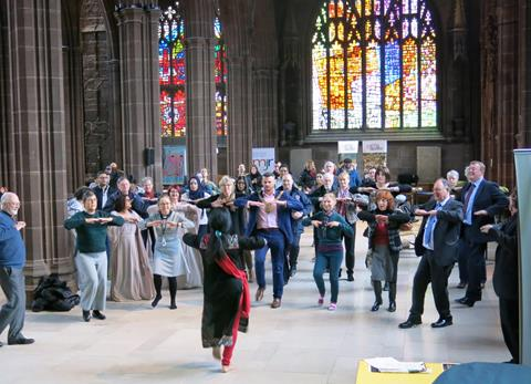 A group of people dancing with stained glass windows in the background