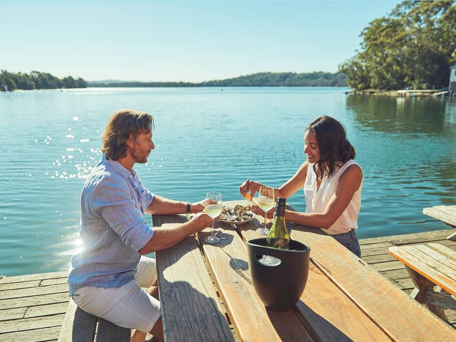 Couple eating oysters outdoors at Eurobodalla