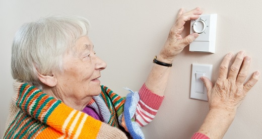 Woman with striped shawl adjusting heat thermostat