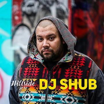 photo of DJ Shub, an Indigenous man. He is looking directly at the camera with a solemn look on his face. He has a shaved head and short beard and moustache. He is wearing a zip-up hoodie with an Indigenous colour pattern on it