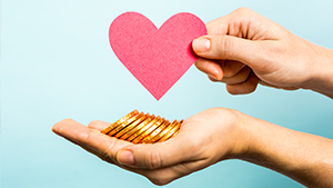 Hand holding coins and heart shaped card