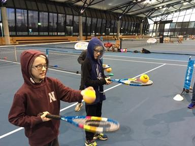 Two young boys with vision impairments bounce large tennis balls on their racquets on an indoor tennis court.