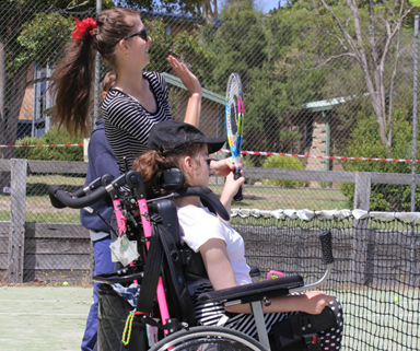 Woman helping a person play tennis
