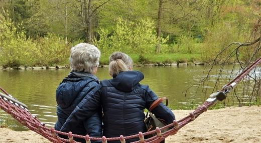 Older women sitting in a hammock by a river