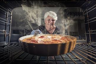 woman pulling pie out of oven