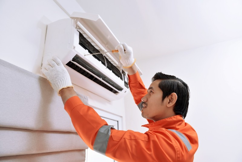 A person in orange safety wear and white gloves is repairing an opened heat pump mounted on a white wall.