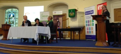 Chairperson and panel on the conferece stage