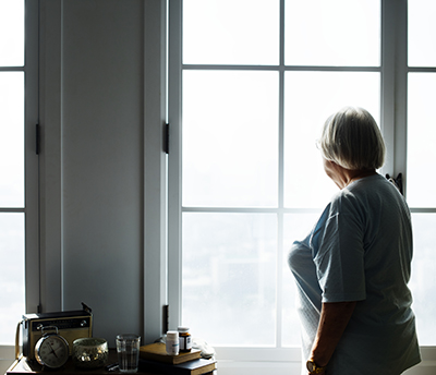 older adult looking out a window