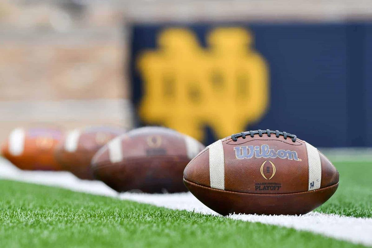 Footballs lined up on the field in front of the Notre Dame logo