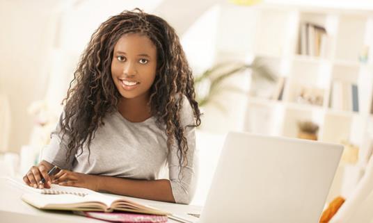 Teen doing her homework using a laptop