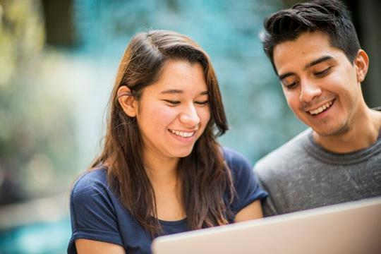 Two students in front of a laptop screen