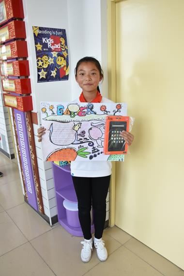 A prize winner shows off her winning poster