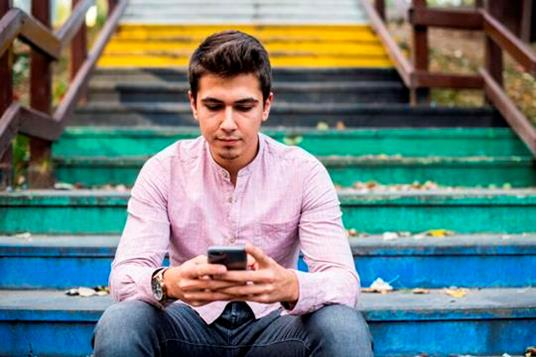 A young adult using his phone