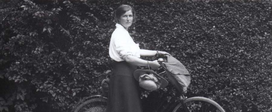 Old black and white photo of lady on a push bike