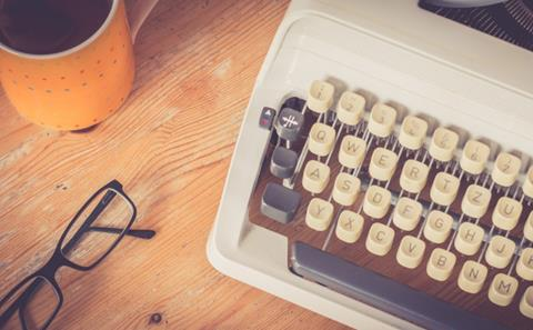 A desk with a coffee mug, glasses, and a typewriter | UTEP Connect | MFA in Creative Writing