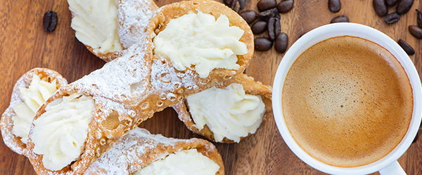 Photo of homemade cannolis and a fresh cup of coffee.