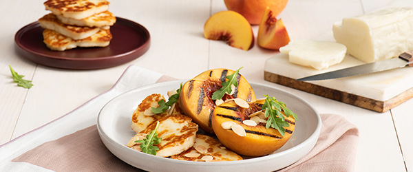 Photo of grilled halloumi with peaches cut in half with grill marks and topped with almonds.