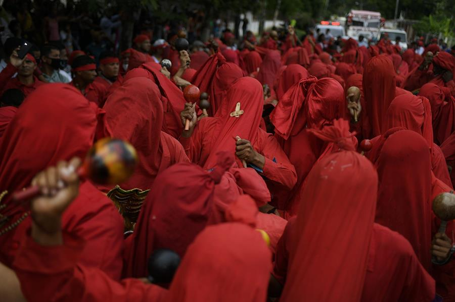Dancing devils shake maracas during Corpus Christi celebrations in San Francisco de Yare, Venezuela, Thursday, June 3, 2021, amid the coronavirus pandemic. They are wearing red robes that cover their faces.
