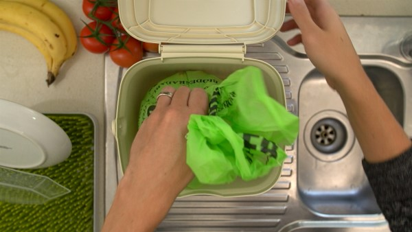 Person using kitchen caddy to recycle food waste