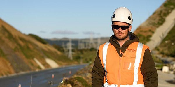 Hamish Tarr wearing a white hard hat and orange hi-vis jacket with Transmission Gully motorway behind him.