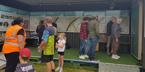 People standing inside and outside the mobile Transmission Gully mobile information centre looking at the maps and information boards.
